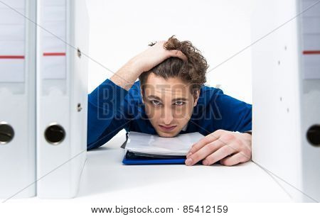 Tired businessman sitting at the table in office
