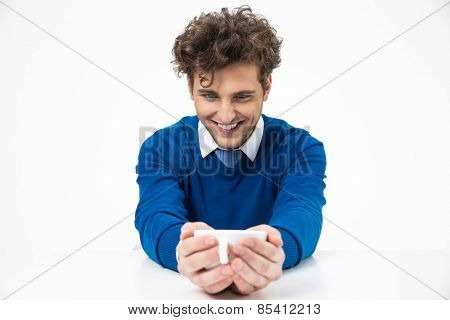 Smiling businessman sitting at the table and holding cup of coffee