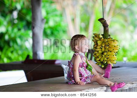 Toddler Girl Outdoors With Bunch Of Bananas
