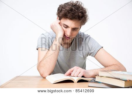 Tired male student sitting at the table with books