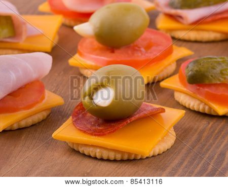 Crackers with cheese, tomato, pepperoni and olives, on dark wood tabletop