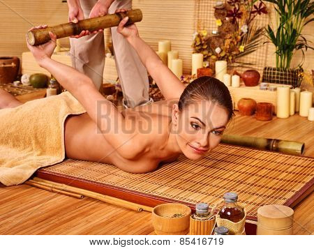 Woman getting bamboo luxury massage. Wooden bed.