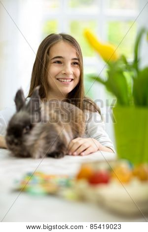 Cute smiling girl siting  for the Easter table with bunny