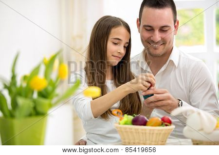 Daughter and father having fun with Easter eggs, breaking colorful eggs