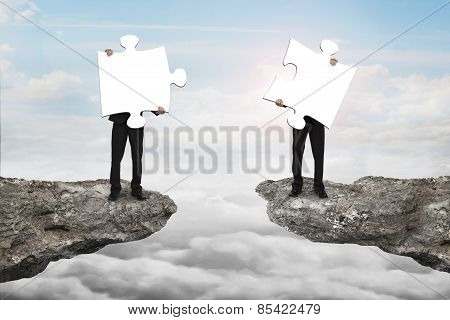 Businessmen Holding Jigsaw Puzzles To Connect On Cliff With Cloudscape