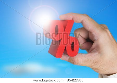Hand Holding 3D Red Percentage Sign With Sky Sunlight