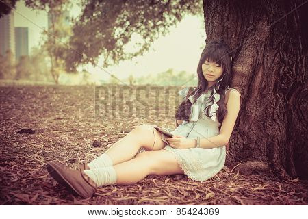 A Cute Asian Thai Girl Is Leaning On A Tree Trunk Sleeping While Listening To The Music With Earphon