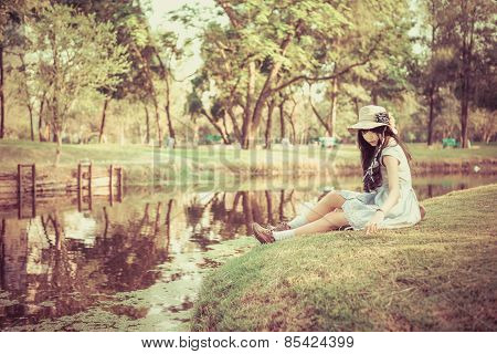 A Cute Asian Thai Girl Is Relaxing Near The Pond In The Wilderness In Vinatge Color.