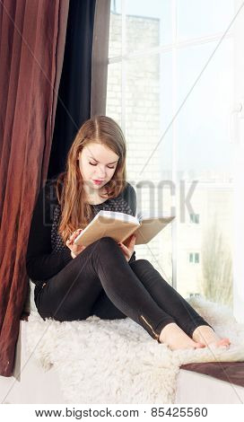 girl reading book near the window.