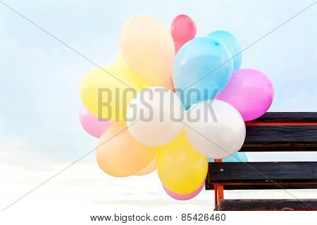 Bunch Of Multicolored Air Balloons Attached To Wooden Bench
