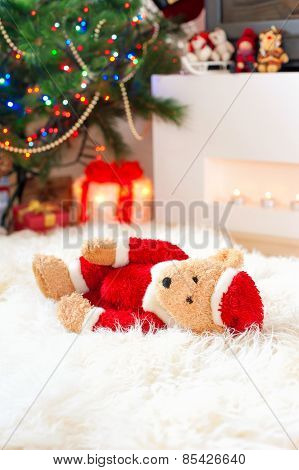 Santa Tedyy Bear Toy Lie On Sheepskin Near Illuminated Christmas Tree