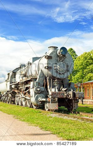 Old Rustic Steam Locomotive On Station Platform. Cloudy Sky Background.