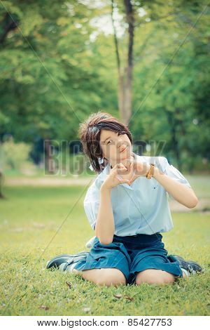 Cute Thai Schoolgirl Is Sitting On The Grass And Doing Heart Symbol In Childish Color.