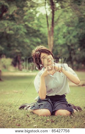 Cute Thai Schoolgirl Is Sitting On The Grass And Doing Heart Symbol In Vintage Color.