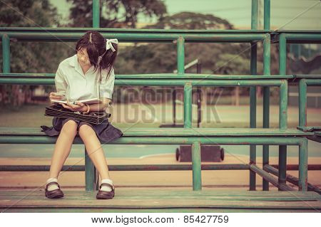 Cute Thai Schoolgirl Is Sitting And Reading On A Stand In Vintage Color