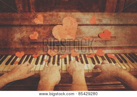 Loving couple playing on piano