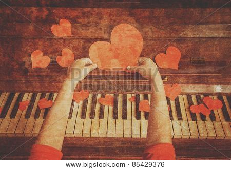Child holding paper heart over the piano