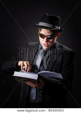 Seriously Teenage Boy Dressed In Suit Reading Book