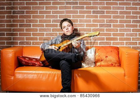 Young Teenage Musician Posing With Guitar