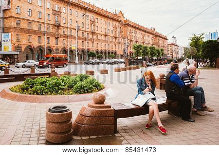 People resting, sitting on bench on Lenin Street in summer in Mi