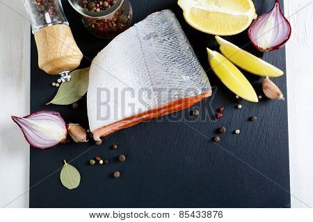 Fresh Salmon Steak On Slate With Lemon And Spices