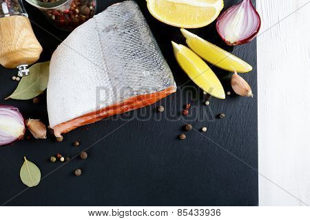 Raw Salmon Steak On Slate With Lemon And Spices