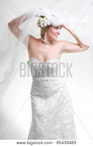 Beautiful Young Woman In A White Dress With A Bouquet Of Flowers