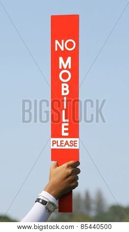 The No Mobile Sign Was Held Up By Volunteer In Golf Tournament.