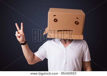 Young man standing and gesturing with a cardboard box on his head with straight face