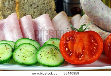 Tasty breakfast - tomatoes, cucumber, ham, white sausage and bread