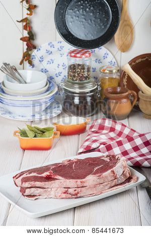 Raw Steaks On The Kitchen Table