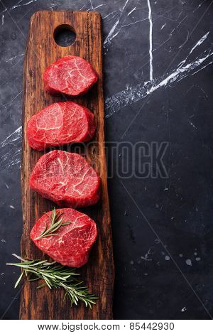 Raw Fresh Marbled Meat Steak And Rosemary On Dark Marble Background