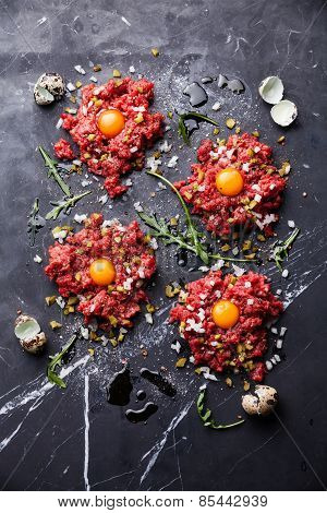 Beef Tartare With Pickled Cucumber And Fresh Onion On Dark Marble Background