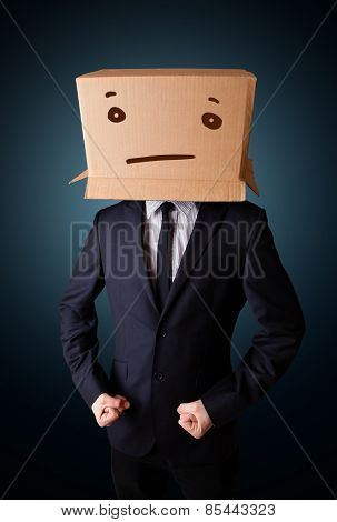 Businessman standing and gesturing with a cardboard box on his head with straight face