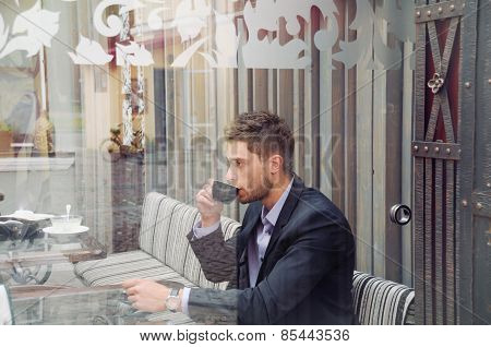 Young Attractive Businessman Drinking Espresso Coffee In The City Cafe During Lunch Time