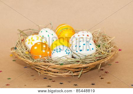 eight easter eggs in basket with hay