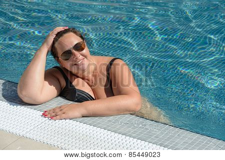 Mid Adult Woman Is At The Edge Of Swimming Pool.