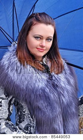 Fashion style young woman holding a big blue umbrella.