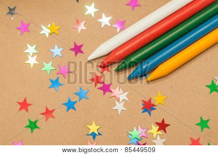 colorful wax crayons and  stars on kraft background