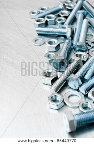 Nuts, washers and bolts on scratched metal background.