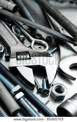 Wrench and tools on the scratched metal background.