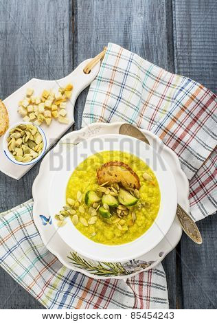 Thick vegetable soup puree with Brussels sprouts, croutons, pumpkin seeds in a white plate