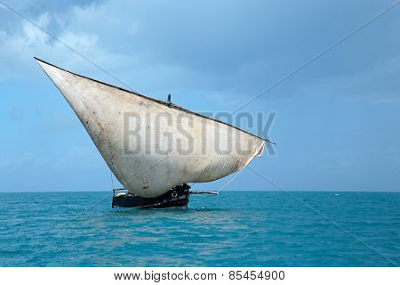 Wooden sailboat (dhow) on water with clouds, Zanzibar island