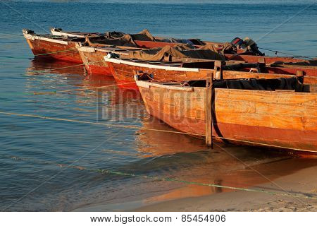 Wooden boats on a beach in late afternoon light, Zanzibar island