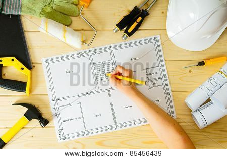 Repair work. Drawings for building, women hand, saw and others tools on wooden background.
