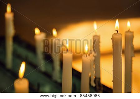 Several church candles against a dark background