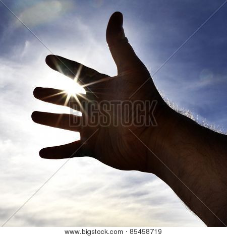 Persons hand reaching in hope towards heaven with sunlight shining through