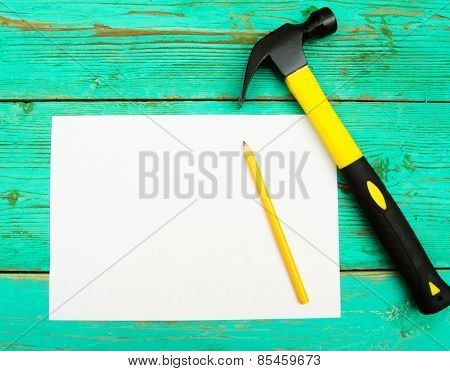Paper with pencil and the working tools on wooden, green background.