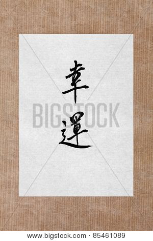 Good fortune chinese calligraphy script on rice paper over brown paper background.