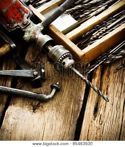 Old drill, a box with drills, pliers and ruler on wooden background.